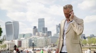 Man talking on phone and city skyline Stock Footage