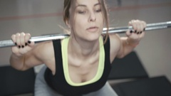 Close up of pretty girl doing squats with heavy barbell in 4K Stock Footage