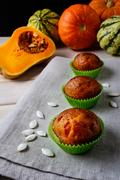 Pumpkin muffins in the green wrappers with squash seeds Stock Photos