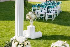 White wedding chairs with green and emerald ribbon outdoors Stock Photos