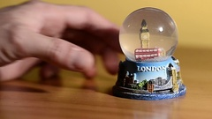 Hand turns a snow globe dedicated to the city of London Stock Footage