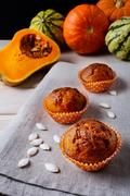 Pumpkin muffins in the orange wrappers with squash seeds Stock Photos