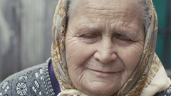 Portrait of old wrinkled tired alone grandmother looking at camera Stock Footage