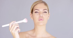 Beautiful young female applying makeup on cheek Stock Footage
