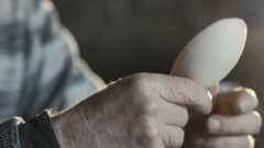 Wrinkled old hands holding handmade wooden spoon Stock Footage