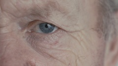Close up of blue eye of old man looking at camera Stock Footage