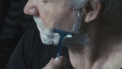 Profile of old gray man shaving beard on face by himself Stock Footage