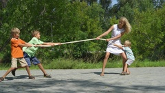 Three happy kids playing tug-of-war in city park with mum. Stock Footage