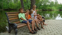 Mother with three kids sitting on the bench and eating apples Stock Footage