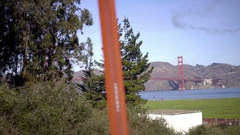 Driving past Golden Gate Bridge from far with smoke chem trail in sky  Stock Footage