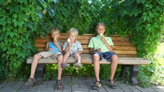 Three boys sitting in park and eating ice cream Stock Footage