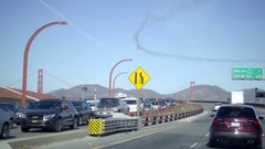 Smoke chem trails sky over San Francisco Golden Gate Bridge cars driving highway Stock Footage