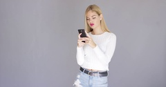 Trendy young blond woman checking her mobile Stock Footage