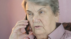 Old woman talking on mobile phone seriously Stock Footage
