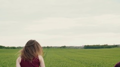 Beautiful woman teases her lover running away in a field, he chases. Happy Stock Footage