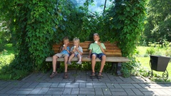 Kids sitting on the bench and eating ice cream Stock Footage