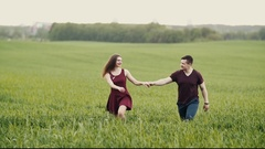 Lovely couple in an oat field. Pretty woman cheerfully jumps as they walk Stock Footage