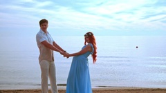 Young people holding hands on sea beach. Pregnant couple beach Stock Footage