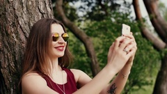 Beautiful brunette woman with red lips takes selfie near a tree, uses her Stock Footage