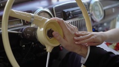 Bride and groom hands on steering wheel of retro car Stock Footage