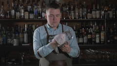 Barman at work rubs a pitcher and glass. Bartender in modern bar Stock Footage