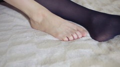 Girl dresses stockings on the bed in the bedroom. close-up Stock Footage