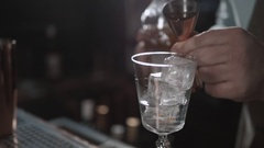 Alcohol flow in a glass with ice. Vodka pouring Stock Footage