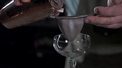 Bartender preparing coctail pouring through sieve close up in bar Stock Footage