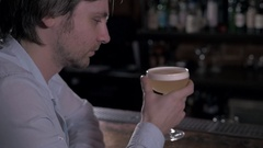 Young man sitting at the bar. Male drink coctail in pub Stock Footage