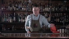 Cheerful male bartender is standing in pub. He is holding cocktail and Stock Footage