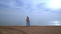 Love couple beach. Pregnant couple hugging on sea beach Stock Footage