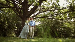 Young, stylish, beautiful pair of newlyweds walking in the park Stock Footage