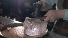 Closeup barman is making cocktail with ice vapor at night club. Ice sphere from Stock Footage