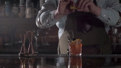 Bartender is adding orange zest to cocktail, barman preparing old fashioned with Stock Footage