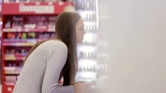 Mother and little daughter selecting goods in beauty secyion at supermarket Stock Footage