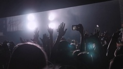 Audience with hands raised at a music festival and lights streaming down from Stock Footage