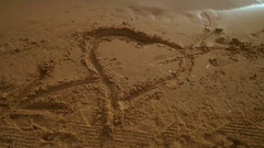 Heart sand. Heart drawing on sand beach. Panning from heart sign on sand to sky Stock Footage