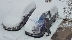 A man clears the snow off the car in the morning after a snowfall Stock Footage