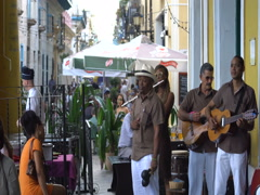 Latino men musicians dressed in white trousers and brown shirt sing, group plays Stock Footage