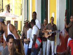 Latino waiters in uniform dance salsa. Men musicians sing and play maracas, Arkistovideo