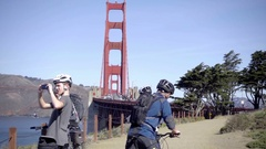 Bicyclist kid taking picture of water by Golden Gate Bridge - tourists on bikes Stock Footage