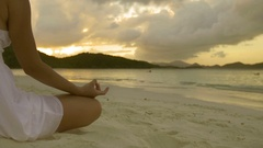 Woman doing yoga meditation on tropical beach at sunset Arkistovideo