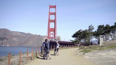 Bicycle tourists taking pictures of Golden Gate Bridge in San Francisco Stock Footage