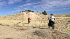 Dirt bikers ride a hill climb HD Stock Footage