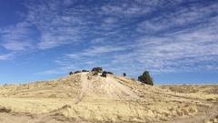 Dirt bikes and ATV ride around desert hills, blue sky HD Stock Footage