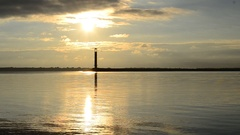 Sunrise over harbor with lighthouse Stock Footage