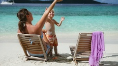 Mother and child playing and relaxing on a tropical beach Stock Footage