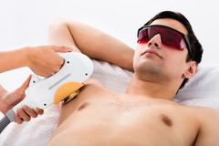 Man Receiving Laser Epilation Treatment On Underarms Stock Photos