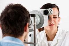 Optometrist Doing Sight Testing For Patient Stock Photos
