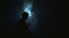 Man exhale electronic cigarette smoke against the dark background Stock Footage